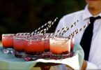 Mann serviert den Bramble Cocktail