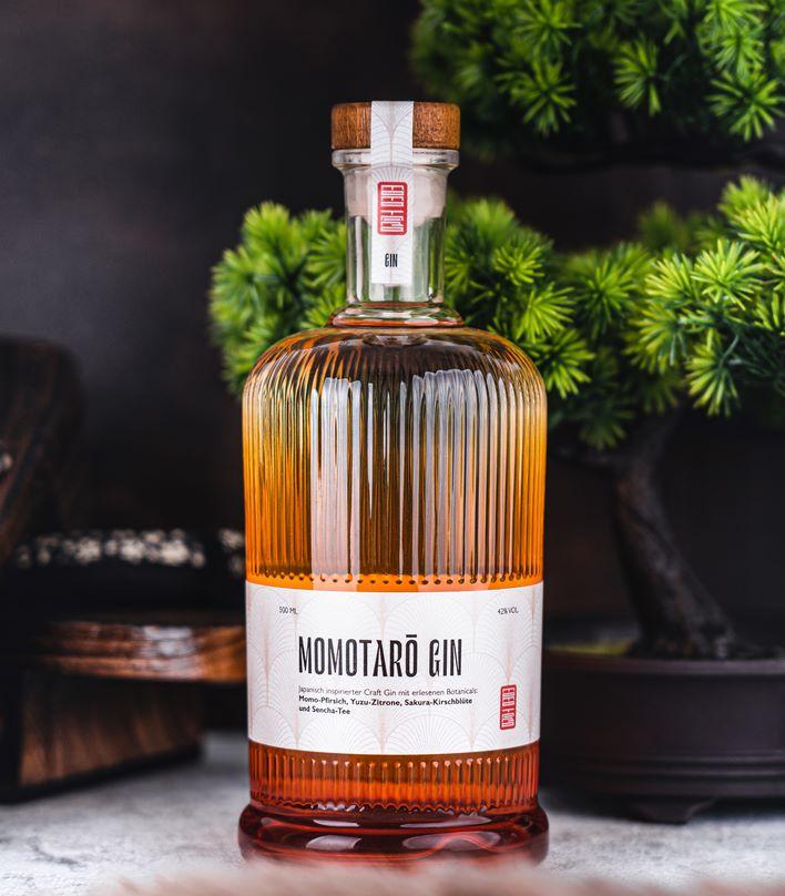 Flasche Momotaro Gin mit Bonsai im Hintergrund